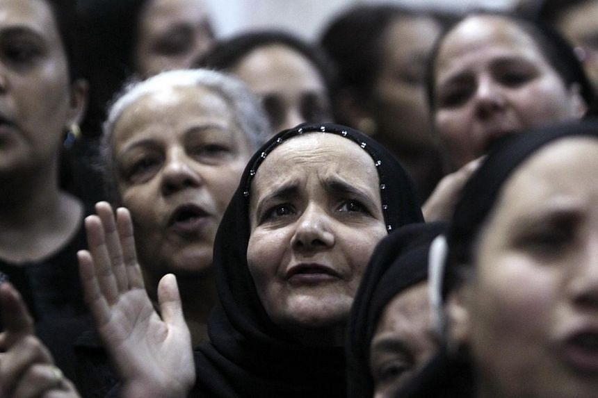 Relatives mourn during the Oct 21, 2013, funeral for four victims killed in an attack at a wedding at Virgin Church in Cairo. Bearded men on a motorcycle pulled up and fired on a crowd waiting for the bride at a wedding on Oct 20, deepening the fears