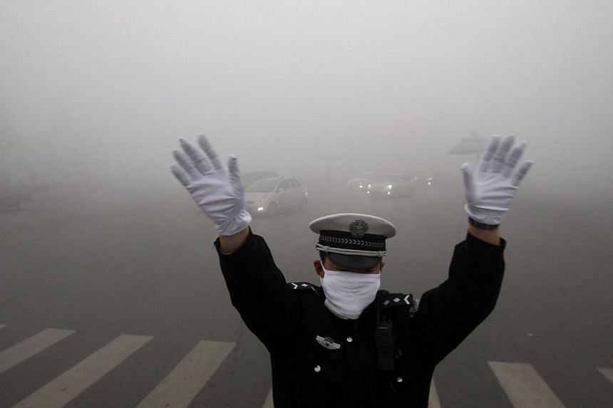 A policeman gestures as he works on a street in heavy smog in Harbin, north-east China's Heilongjiang province, on Oct 21, 2013. Thick smog enveloped a Chinese city for a third day on Tuesday, with schools and a regional airport shuttered and low vis