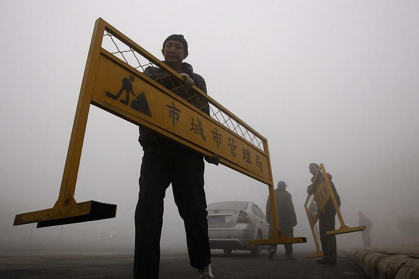 A workman carries a road barrier on a street under heavy smog in Harbin, north-east China's Heilongjiang province, on Oct 21, 2013. -- PHOTO: AFP