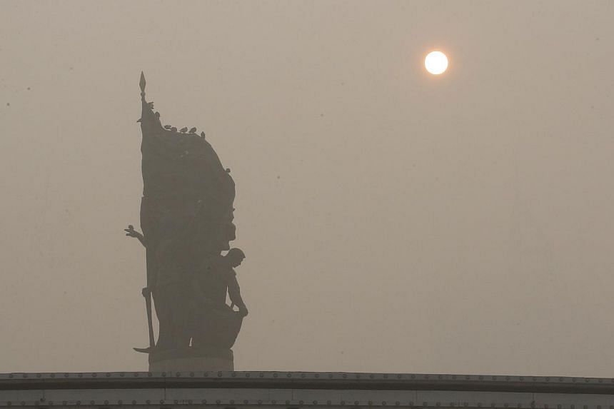 A statue is seen under heavy smog in Harbin, north-east China's Heilongjiang province, on Oct 21, 2013. -- PHOTO: AFP