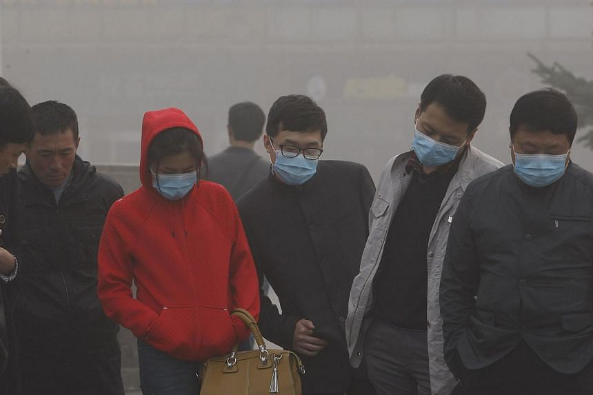 Residents with masks on their faces are seen under heavy smog in Harbin, north-east China's Heilongjiang province, on Oct 21, 2013. -- PHOTO: AFP