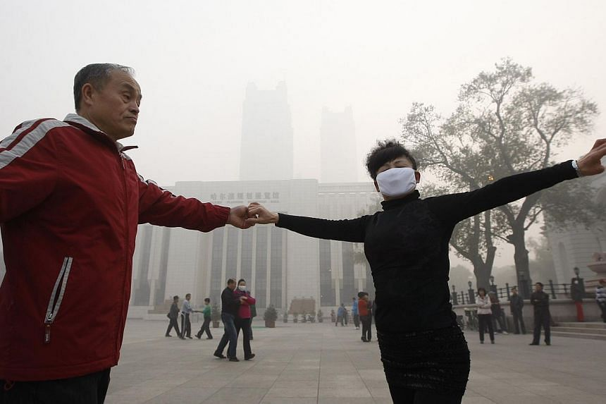 Local residents dance on a square under heavy smog in Harbin, north-east China's Heilongjiang province, on Oct 21, 2013. -- PHOTO: AFP