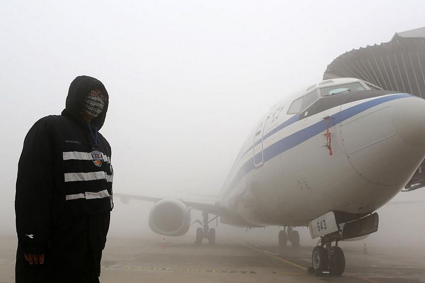 A man stands next to an airplane under heavy smog in Harbin, north-east China's Heilongjiang province, on October 21, 2013. -- PHOTO: AFP