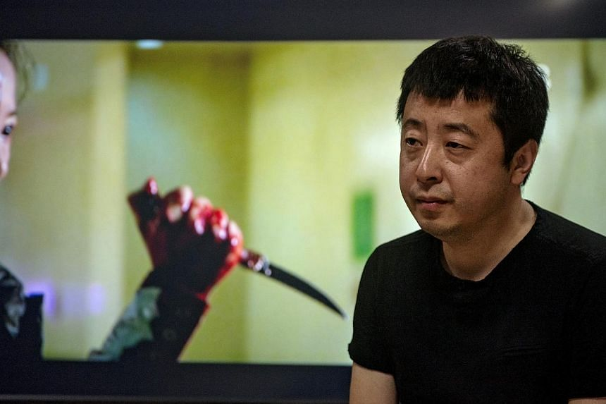 """Director Jia Zhangke at his office, in front of an image from his latest film """"A Touch of Sin,"""" in Beijing, on Aug. 15, 2013. Reports of ordinary Chinese being driven to violence persuaded the director to put aside his first big-budget martial arts f"""