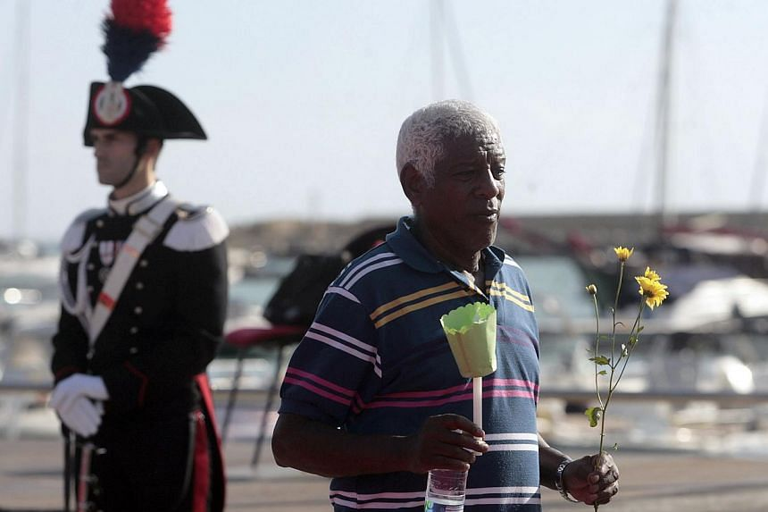 A man holds flowers on Oct 21, 2013 in the southern Sicilian city of Agrigento during a ceremony commemorating the migrants who drowned off the southern Italian islad of Lampedusa. -- PHOTO: AFP
