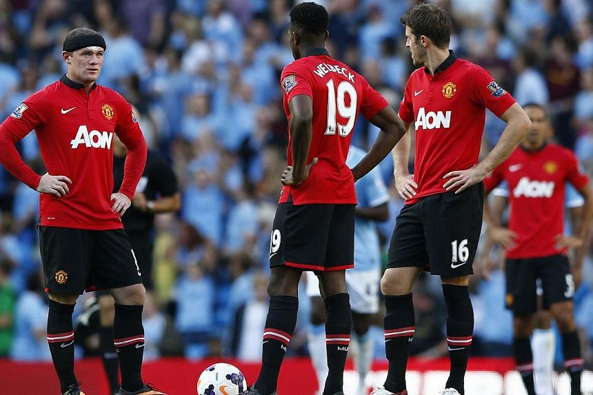 Manchester United's Wayne Rooney (left), Danny Wellbeck (centre) and Michael Carrick prepare to kick off after Manchester City's Sergio Aguero (unseen) scored during their English Premier League soccer match at the Etihad Stadium in Manchester, north