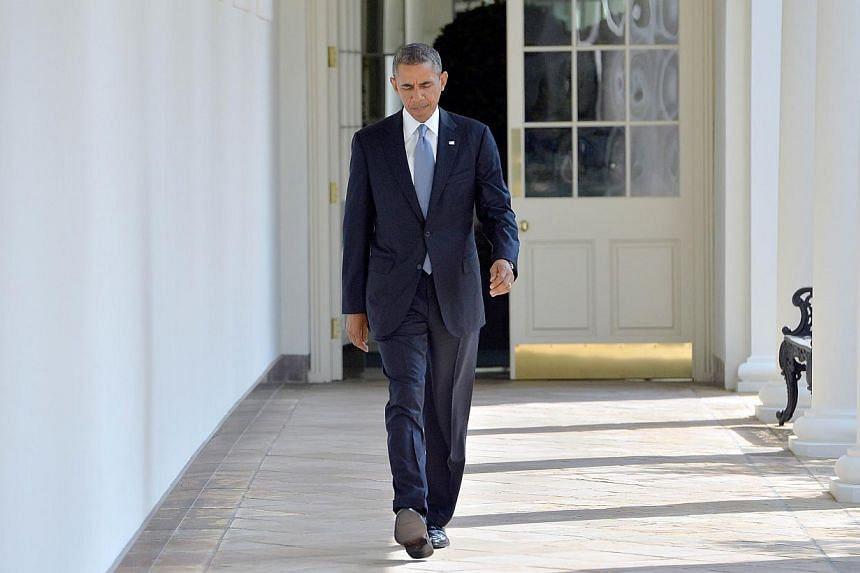 US President Barack Obama walks along the colonnade at the White House to the Oval Office on Sept 10, 2013 in Washington, DC. Mr Obama spoke to France's President Francois Hollande on Monday as a row raged between the long-time allies over claims a U