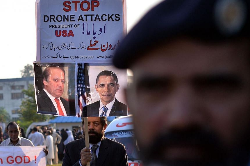 Pakistani Christian minority leader J. Salik (centre) holds a placard with the posters of the US President Barack Obama and Pakistani Prime Minister Nawaz Sharif, during a protest in Islamabad on Oct 21, 2013, against US drone attacks in the Pakistan