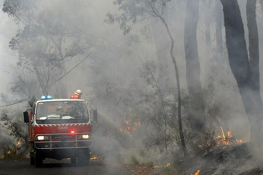 Rural Fire Service firefighters spray water onto a small fire burning near a home in the Blue Mountains suburb of Faulconbridge, located around 80km west of Sydney, on Oct 22, 2013. See more pictures from around the world in Through The Lens' Today i