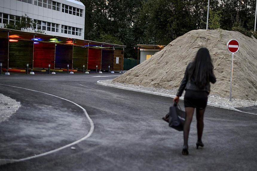 "A prostitute walks past so-called ""sex boxes"" at the opening day of Switzerland's first sex drive-in on Aug 26, 2013 in Zurich, which is aiming to get prostitution off the city streets. -- PHOTO : AFP"