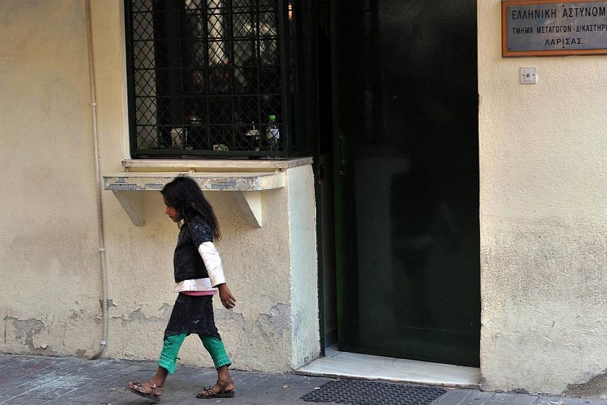 """A Roma girl walks on October 21, 2013 outside the courthouse of the central Greek city of of Larissa, where a Roma couple is due to appear in court on charges of abducting a young girl dubbed the """"blonde angel"""", whose discovery has prompted thousands"""