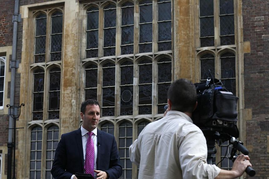 A television crew report from outside the Chapel Royal, St James's Palace in London ahead of the christening of Prince George, Tuesday, Oct 22, 2013. -- PHOTO: AP