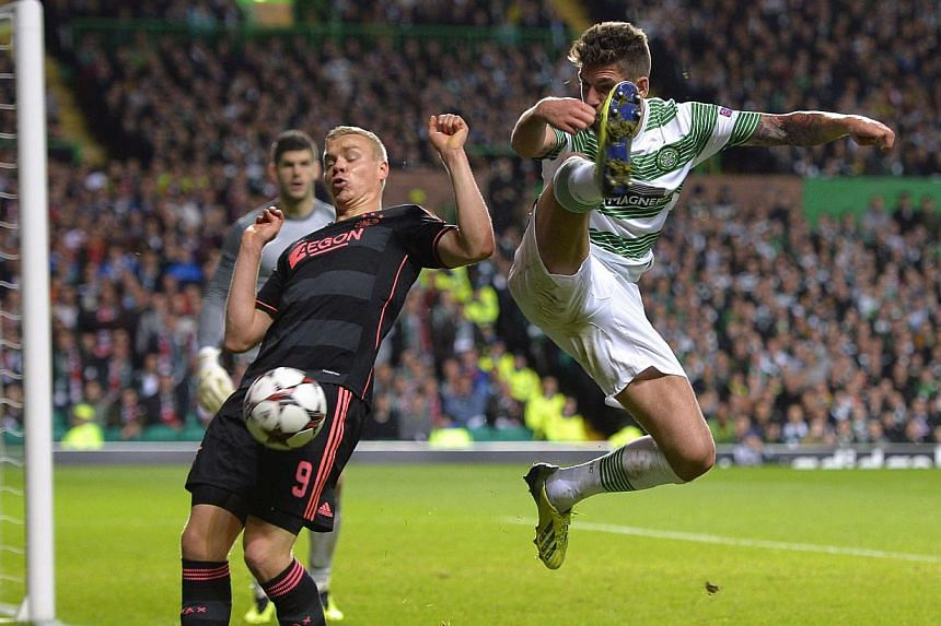 Celtic's Charlie Mulgrew (right) challenges Ajax's Kolbeinn Sigthorsson during their Champions League soccer match at Celtic Park Stadium, Scotland October 22, 2013.   Celtic won the game 2-1. Celtic kick-started their Champions League