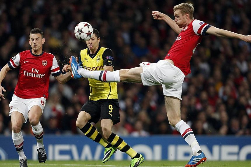 Borussia Dortmund's Polish striker Robert Lewandowski (C) vies with Arsenal's German defender Per Mertesacker (R) and French defender Laurent Koscielny (L) during the UEFA Champions League Group F football match between Arsenal and Borussia Dortmund