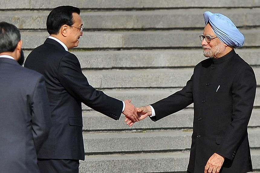Chinese Premier Li Keqiang (second left) shakes hands with India's Prime Minister Manmohan Singh (right) during a welcoming ceremony outside the Great Hall of the People in Beijing on Oct 23, 2013. China and India took a small step towards improving