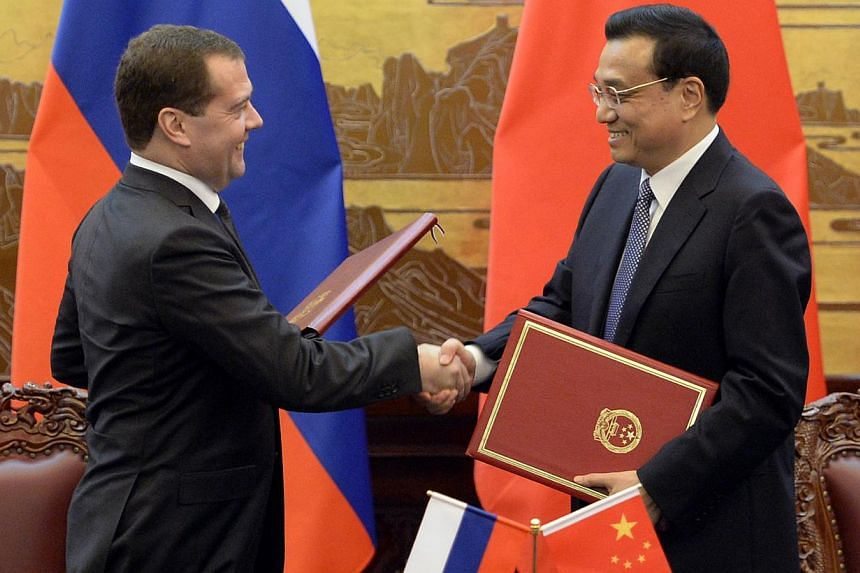 "Russian Prime Minister Dmitry Medvedev (left) shakes hands with Chinese Premier Li Keqiang during a signing ceremony at the Great Hall of the People in Beijing, China on Tuesday, Oct 22, 2013. Chinese state media hailed the ""huge potential"" of t"