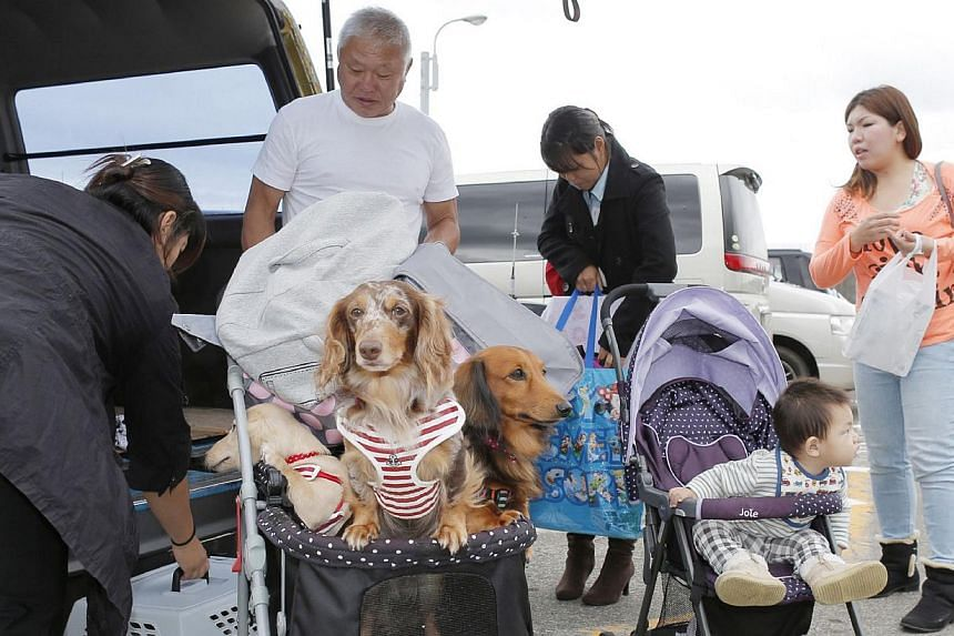 People arrive at the Okada port before evacuating Oshima island on Wednesday, Oct 23, 2013, ahead of the arrival of another powerful typhoon.More than 50 people were being evacuated from a storm-battered Japanese island on Wednesday, where muds