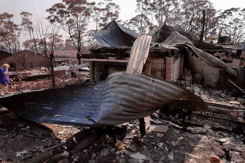 Local resident Delia Smith (left) reacts as she inspects her family's house with her husband Colin after it was destroyed by a bushfire in the Blue Mountains suburb of Winmalee, located around 70km west of Sydney, on Oct 21, 2013. -- PHOTO: REUTERS
