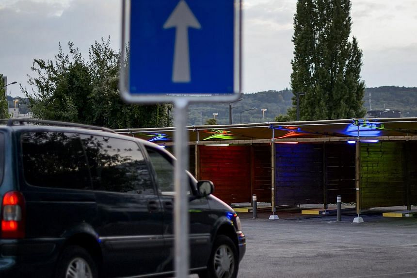 "A car moves next to the so-called ""sex boxes"" on the opening day of Switzerland's first sex drive-in on Aug 26, 2013 in Zurich, which is aiming to get prostitution off the city streets. Switzerland's first sex drive-in, which opened two months ago, h"