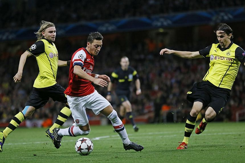Borussia Dortmund's Henrikh Mkhitaryan (right) scores a goal against Arsenal during their Champions League soccer match at the Emirates stadium in London on Oct 22, 2013. Dortmund beat Arsenal 2-1. -- PHOTO: REUTERS