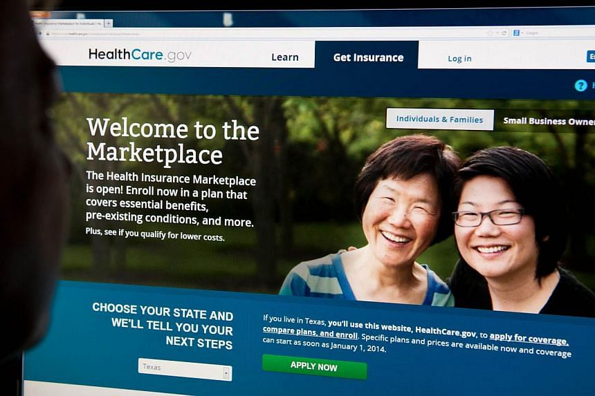 """A woman looks at the HealthCare.gov insurance exchange internet site in this Oct 1, 2013 file photo in Washington, DC. With America's budget battles over at least until December, Republicans stepped up attacks against their favourite target """"Obamacar"""