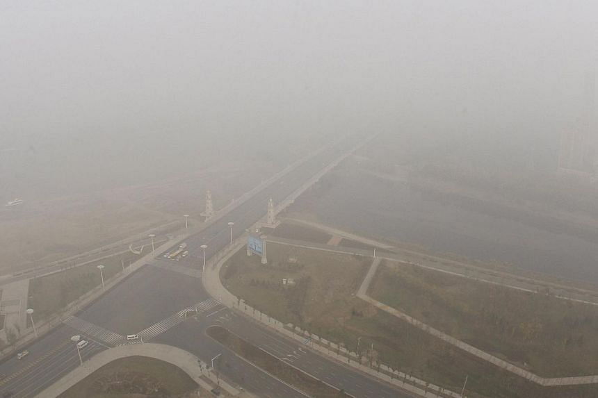 Streets are seen under heavy smog in Harbin, north-east China's Heilongjiang province, on Oct 22, 2013. Flights resume and children are going back to school on Oct 23 as smog eases in Harbin. -- FILE PHOTO: AFP