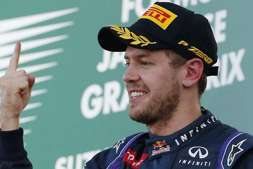 Red Bull driver Sebastian Vettel of Germany celebrates after winning the Japanese Formula One Grand Prix at the Suzuka circuit in Suzuka, Japan, on Oct 13, 2013. Vettel has pledged to keep pushing until the very end as he aims to secure an amazing fo