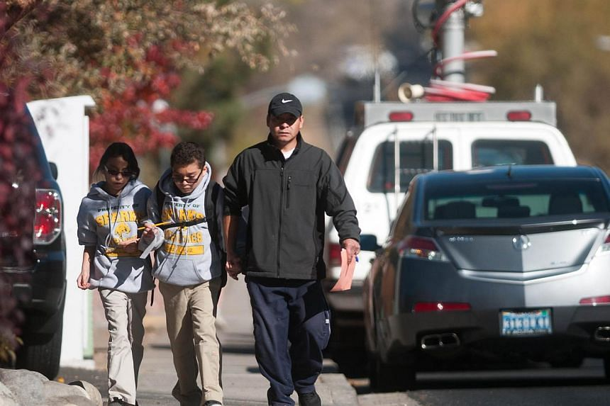 A parent escorts his children from Agnes Risley Elementary school following a shooting at nearby Sparks Middle School on Oct 21, 2013 in Sparks, Nevada. A 13-year-old California boy carrying a replica of an assault rifle was shot and killed by sherif