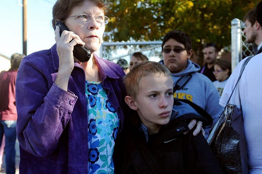 Parents pick up their students at Sparks High after a shooting at Sparks Middle School in Sparks, Nevada, on Oct 21, 2013. A 13-year-old California boy carrying a replica of an assault rifle was shot and killed by sheriff's deputies who apparently be