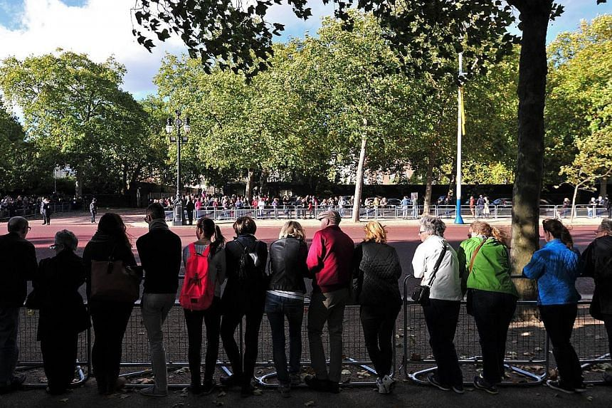 Royal supporters look out towards St James's Palace in central London on Oct 23, 2013, where Prince George of Cambridge will be baptised inside Chapel Royal. Britain's Prince William and his wife Catherine named the godparents for their baby son Prin