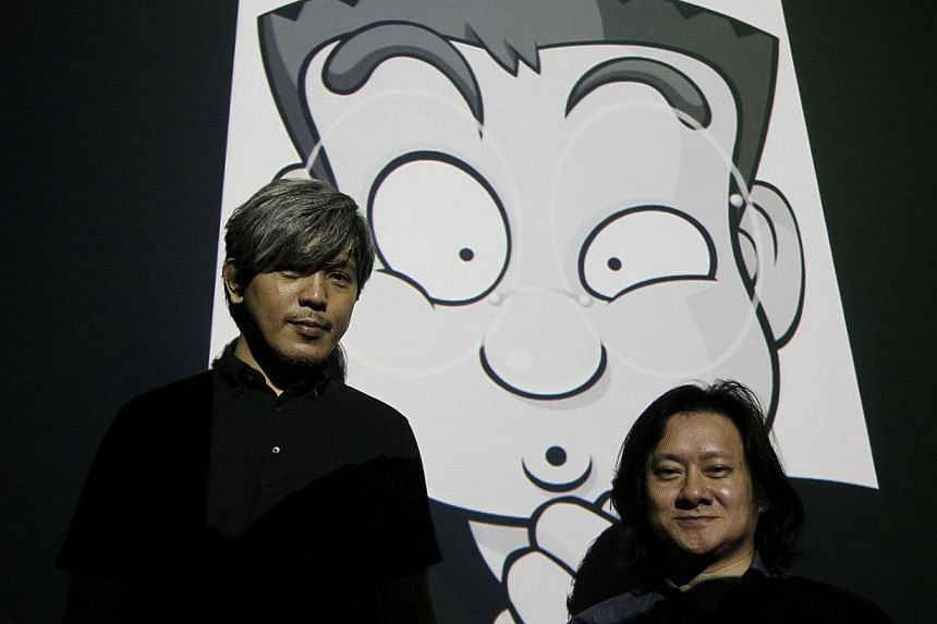 Mr Kiasu creator Johnny Lau (right) and co-artist Nick Tan are coming up with a comic book titled Everything Also Want To Be S.U.R.E. Behind them is a projection of a page from the book.