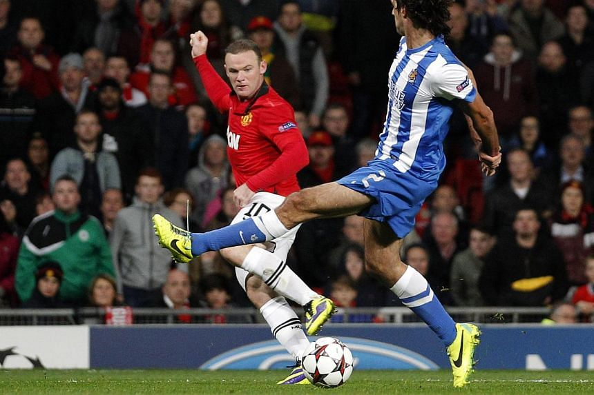 Manchester United's Wayne Rooney, left, keeps the ball from Real Sociedad's Carlos Martinez during the Champions League group A soccer match between Manchester United and Real Sociedad in Manchester, England, on Wednesday, Oct. 23, 2013. Manchester U