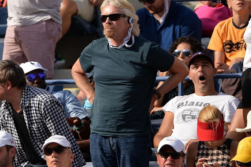 Mr  Richard Branson (centre), founder of Virgin Group, watches the men's seminfinal match between Novak Djokovic of Serbia and Stanislas Wawrinka of Switzerland during the 2013 US Open at the USTA Billie Jean King National Tennis Center on Sept