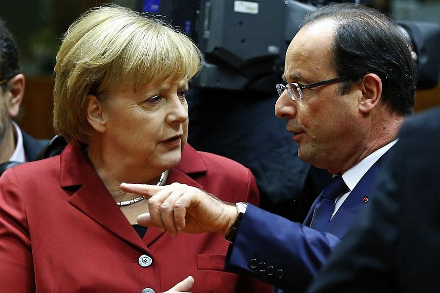 Germany's Chancellor Angela Merkel (left) talks with France's President Francois Hollande at a European Union leaders summit in Brussels on Oct 24, 2013.France and Germany want talks to agree new rules for intelligence relations with the
