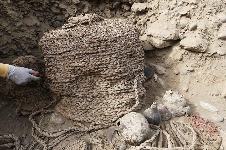 An archaeologist cleans the recently discovered tomb of an intact mummy of the Wari prehispanic culture in Lima's Huaca Pucllana ceremonial complex, at Miraflores district, October 24, 2013.Two pre-Columbian mummies more than a thousand years o