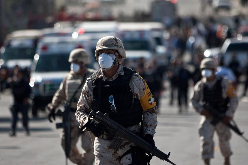 Soldiers arrive at the scene after the boiler of a United States-owned candy factory exploded in Ciudad Juarez, in northern Mexico, on Oct 24, 2013. The huge blas thatt rocked the Blueberry factory caused the ceiling to collapse, injuring more than 4
