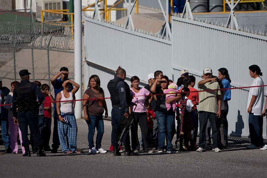 Relatives and friends of workers wait for news after the boiler of a United States-owned candy factory exploded in Ciudad Juarez, in northern Mexico, on Oct 24, 2013. The huge blas thatt rocked the Blueberry factory caused the ceiling to collapse, in