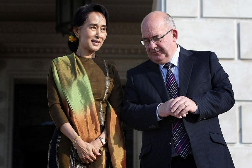 Myanmar opposition leader Aung San Suu Kyi (left) is greeted by the Speaker of the Assembly William Hay (right) as she arrives at Stormont Parliament building in Belfast, Northern Ireland, on Oct 24, 2013. -- PHOTO: AFP