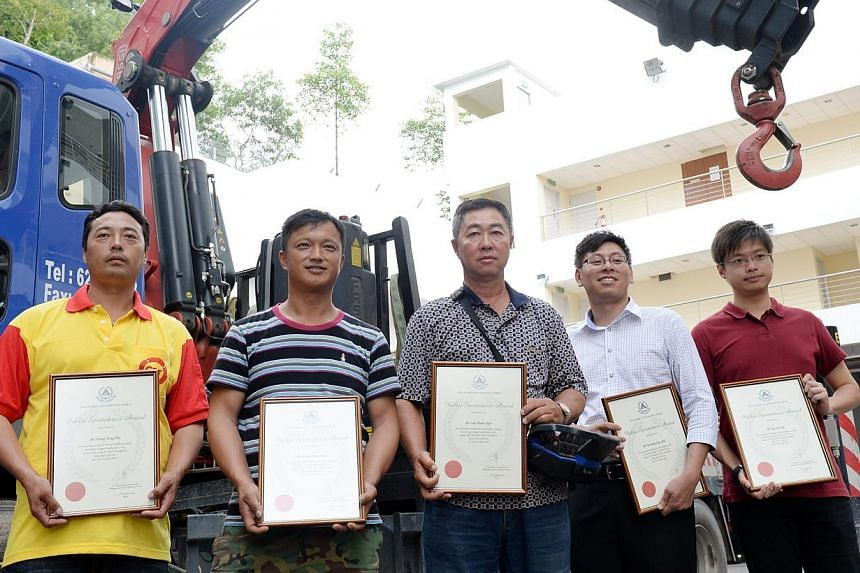 (From left) Mr Zhang Yonghui, Mr Gong Ming Shan, Mr Lim Thiam Ngor, Mr Alex Yeoand Mr Tay Wei Jiehold their SCDF Public Spiritedness Awards for rendering assistance in the accident along the Ayer Rajah Expressway on Friday, Oct 25, 2013.&