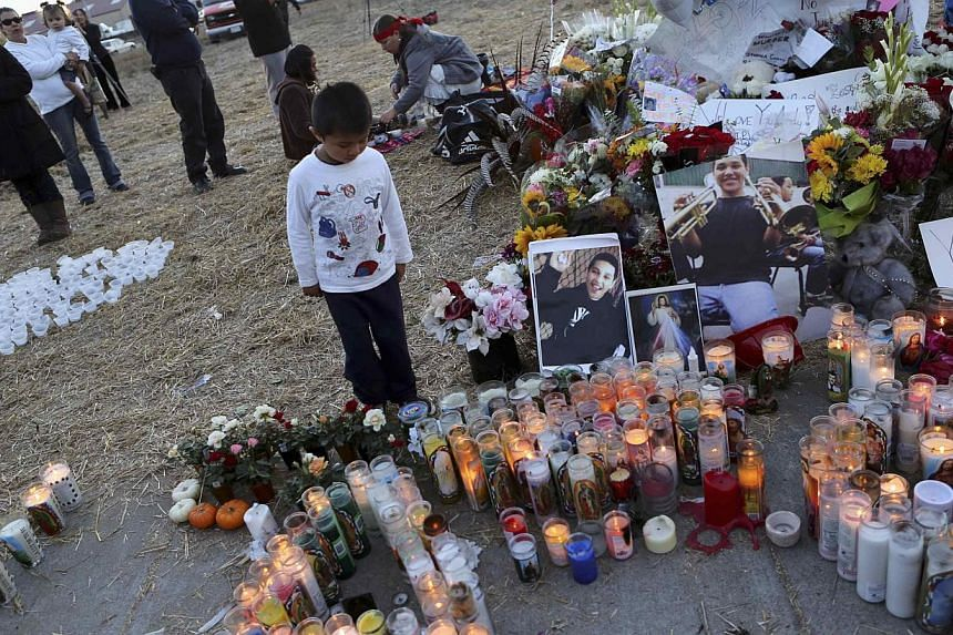 A child looks over a makeshift memorial for Andy Lopez Cruz at the site of his death in Santa Rosa, California on Thursday, Oct 24, 2013. -- PHOTO: REUTERS
