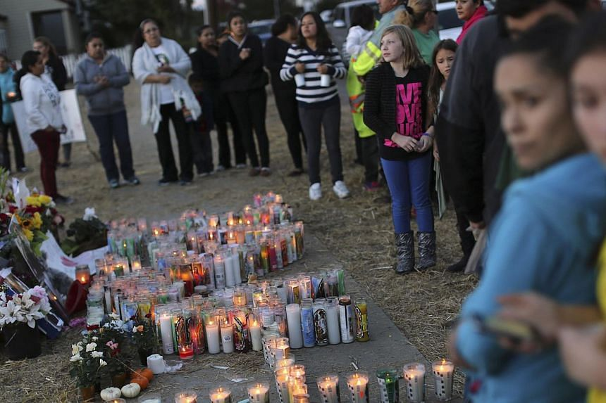 People look over a makeshift memorial for Andy Lopez Cruz at the site of his death in Santa Rosa, Californiaon Thursday, Oct 24, 2013. -- PHOTO: REUTERS