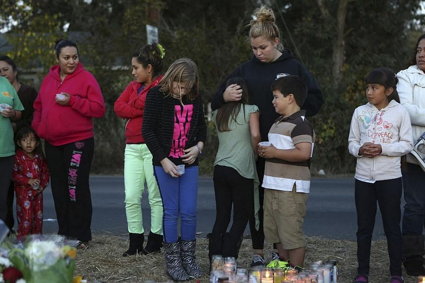 Children stand at a makeshift memorial for Andy Lopez Cruz at the site of his death in Santa Rosa, Californiaon Thursday, Oct 24, 2013. -- PHOTO: REUTERS