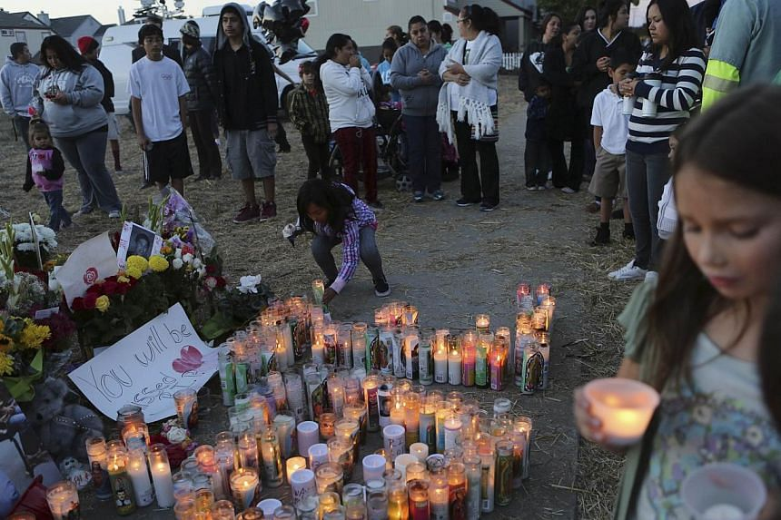 A young girl places a candle on a makeshift memorial for Andy Lopez Cruz at the site of his death in Santa Rosa, Californiaon Thursday, Oct 24, 2013. -- PHOTO: REUTERS
