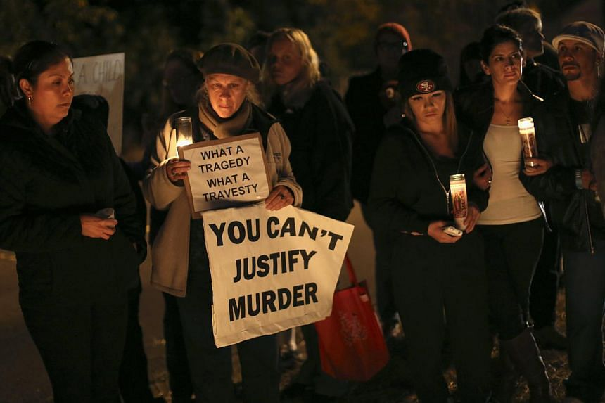 People hold signs and candles at a makeshift memorial for Andy Lopez Cruz at the site of his death in Santa Rosa, Californiaon Thursday, Oct 24, 2013. -- PHOTO: REUTERS