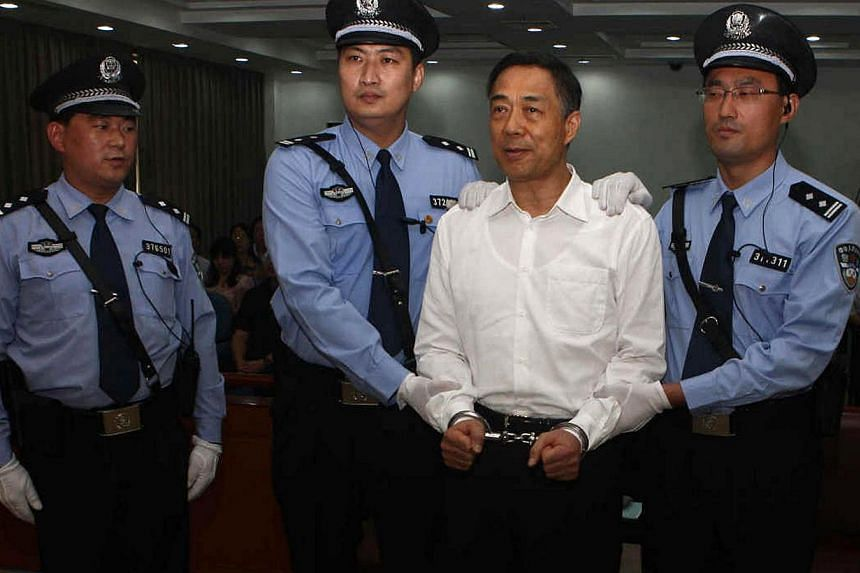 This picture taken on Sept 22, 2013 and released by Jinan Intermediate People's Court shows Chinese political star Bo Xilai (second, right) wearing a pair of handcuffs as he stands in a courtroom in Jinan, east China's Shandong province. A Chinese co