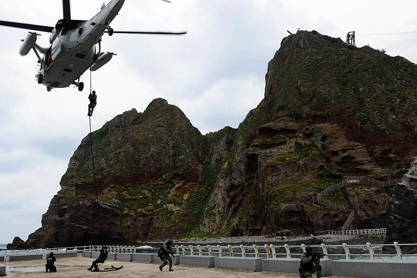 This handout photo taken on October 25, 2013 shows South Korean Navy's Underwater Demolition Team members conducting a landing operation on the tiny chain of Seoul-controlled rocky islands, known as Dokdo in Korea and Takeshima in Japan, in the Sea o