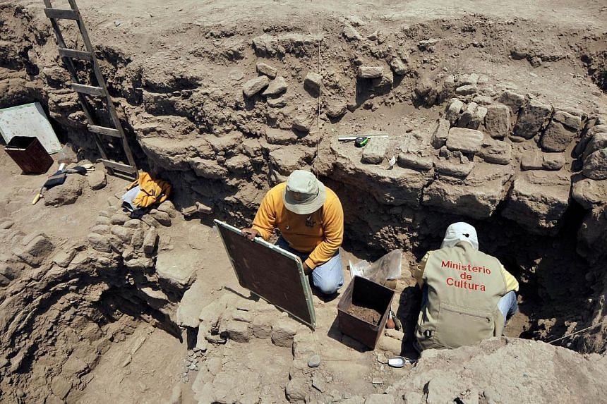 """Archaeologists work at the pre-Inca religious complex """"Huaca Pucllana"""", in the residential district of Miraflores, in Lima, on Oct 24, 2013 - day in which archaeologist Gladys Paz informed that two pre-Columbian mummies of over a thousand years old,"""