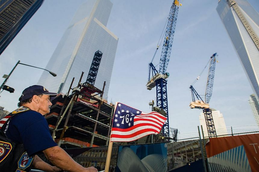 Mr Jose Gonzales, of New York, takes a minute to reflect in front of One World Trade Center, right, during the 12th anniversary observance of the 9/11 terror attacks, on Wednesday, Sept 11, 2013 in New York. The chief prosecutor at Guantanamo Bay pro