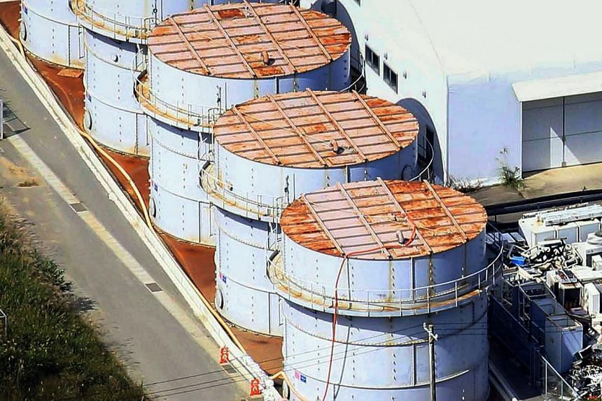 In this Oct 3, 2013 aerial file photo, the storage tank, bottom, which workers detected the water dripping from the top, at the Fukushima Dai-ichi nuclear plant at Okuma town in Fukushima prefecture, north-eastern Japan. The operator of Japan's wreck