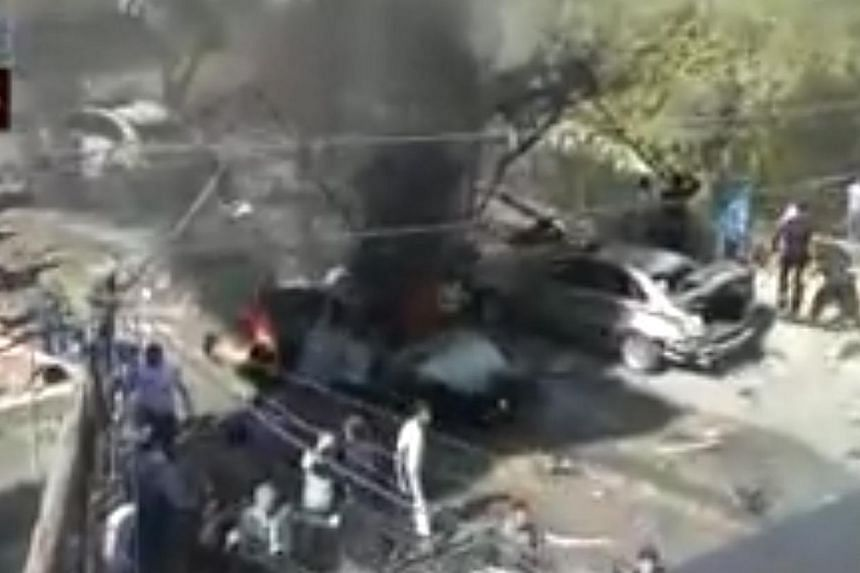 An image grab taken from a video uploaded on YouTube and provided by Nabad al-Aasima (Capital Pulsation) non profit organization on October 25, 2013 allegedly shows people gathering on the site of a car bomb attack outside a mosque in the town of Suq